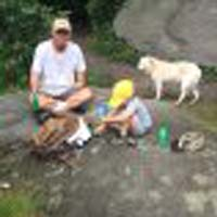 man and a child camping with dog